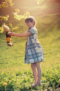 girl holding teddy bear outside