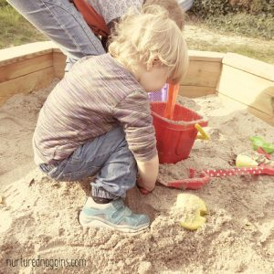 little boy toddler playing in sandbox