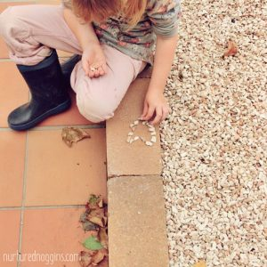 child making heart with rock pebbles