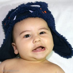 silly baby wearing fuzzy blue hat